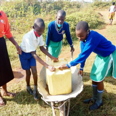 PUPILS PUSHING WATER ON A WHELLBARROW