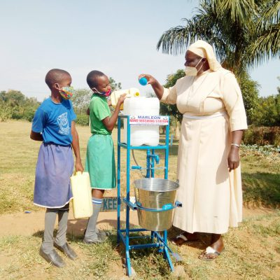 SR. LAETITIA, THE HEADTEACHER GUIDING GIRLS ON REFILLING THE HANDWASHING FACILITY WITH WATER