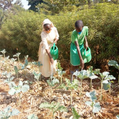 SR. SUZAN AND A PUPIL WATERING A VEGETABLE GARDEN USING WATER FROM THE COMMUNITY SPRING WELL
