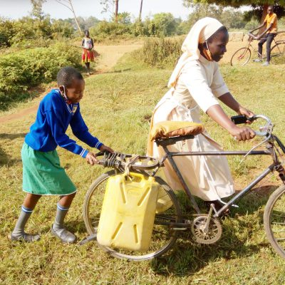 SR. SUZAN SUPPORTED BY A PUPIL PUSHING A BICYCLE LOADED WITH WATER